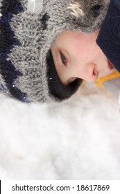 Cute little boy laying in the snow