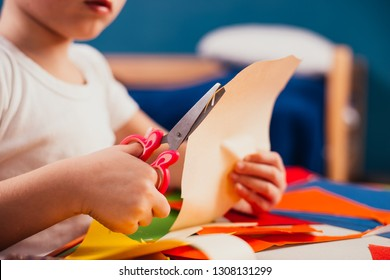 Cute little boy learning how to use the scissors cut paper,Schoolboy showing how to use scissors cutting paper,Children learn and play at home, Home school concept