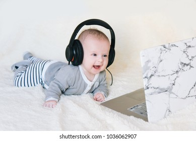 Cute little boy lies on his stomach in headphones and looks in laptop, selective focus