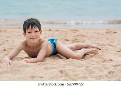 Cute little boy lies on the sand on the seashore happy