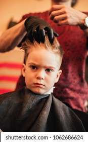 Cute little boy is looking at camera while getting haircut by hairdresser at the barbershop