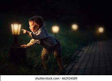 Cute little boy looking and magic light of a lantern in the evening. Image with selective focus and toning
