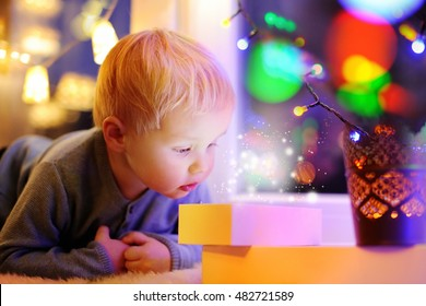 Cute little boy looking on a magical Christmas or New Year gift lying on window sill. Winter holidays concept