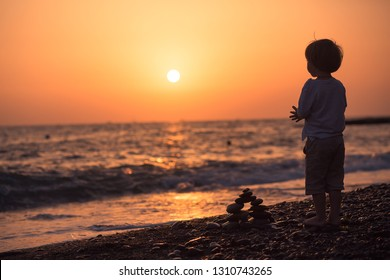Cute little boy is looking at the sunset sky on the pebble beach. Image with selective focus and toning