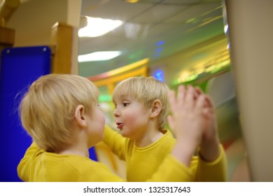 Cute little boy looks in distorting mirror in play center. Child playing on indoor playground.