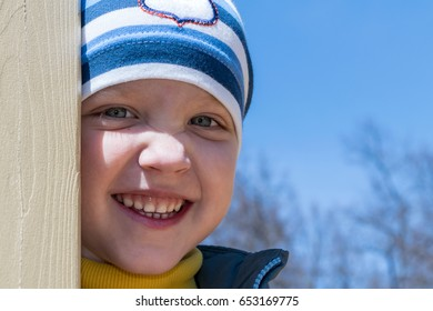 Cute little boy looks up and smiles. His cheerful mood. He plays on the Playground. The boy wears a sweater, jacket and hat. He peeks out from behind a wooden support slide.