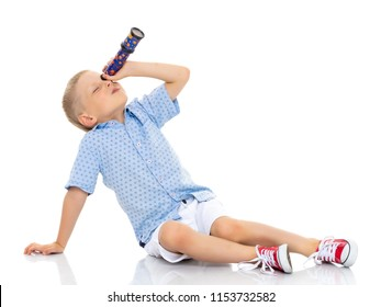 A cute little boy looks through a telescope or kaleidoscope. The concept of studying outer space and the surrounding world, a scientific discovery. Isolated on white background.