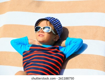 cute little boy lying on a beach towel on summer beach