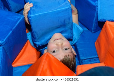 Cute little boy lying on his back playing amongst colorful red and blue plastic cubes grinning up at the camera