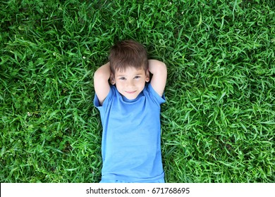 Cute little boy lying on green grass in park