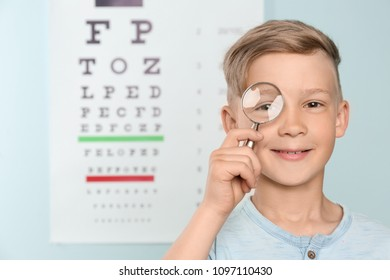 Cute little boy with magnifier in ophthalmologist office