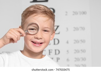 Cute little boy with magnifier in ophthalmologist's office