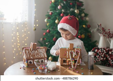 Cute little boy, making gingerbread cookies house, decorating at home in front of the Christmas tree, child playing and enjoying, Christmas concept
