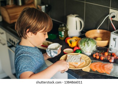 Cute little boy making salmon sandwich with fresh ingredients, spreading cream cheese on toast bread