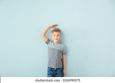 Cute little boy measuring height near color wall
