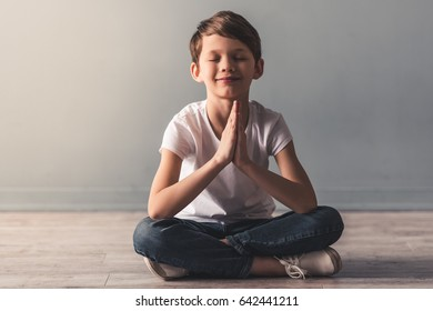 Cute little boy is meditating and smiling while sitting in lotus position on the floor