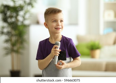 Cute little boy with microphone at home