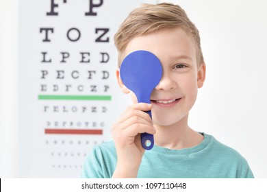 Cute little boy near eye chart in ophthalmologist office