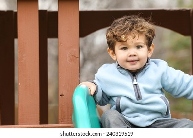Cute little boy on the slide at the park.