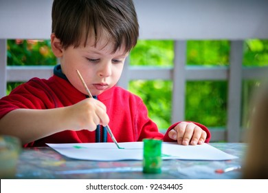 Cute little boy painting with brush