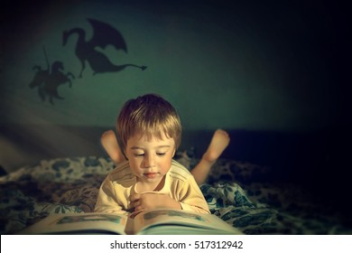 Cute little boy in pajama reading a book on a bed about dragons and knights.Image with selective focus and toning