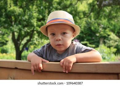 Cute little boy, peeking over a fence.