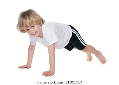 A cute little boy performs gymnastic exercises on the white background