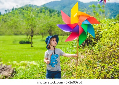 Cute little boy and a pinwheel windmill. the concept of childhood