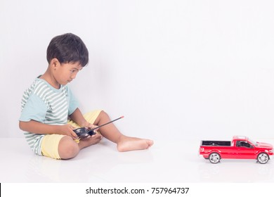 cute little boy play semi-automatic toy car on white background
