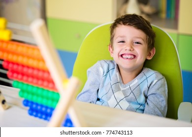 Cute little boy playing with abacus at home. Preschooler having fun with educational toy at home or kindergarten. Smart child learning to count.