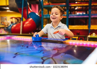 Cute little boy playing air hockey at Arcade centre