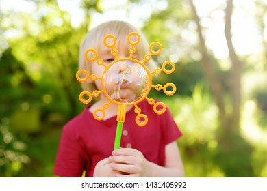 Cute little boy is playing with big bubbles outdoor. Child is blowing big and small bubbles simultaneously. Active summer leisure for kids.