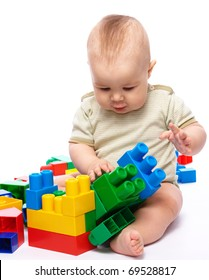 Cute little boy is playing with building bricks while sitting on floor, isolated over white