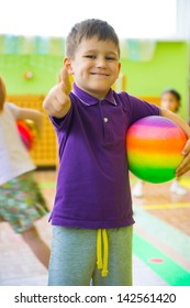 Cute little boy playing at daycare gym with ball