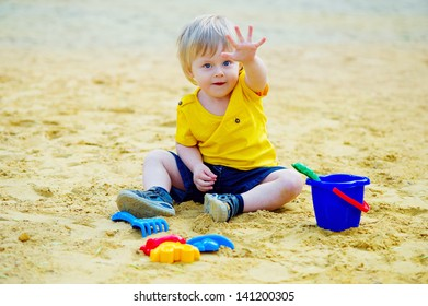 Cute little boy playing with his toys in the sandpit