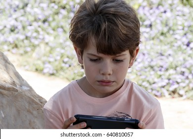 Cute little boy playing with mobile device