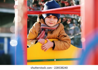 cute little boy playing on the playground, autumn time