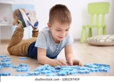 Cute little boy playing with pazzles at home