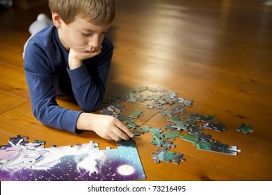 Cute little boy playing with puzzle