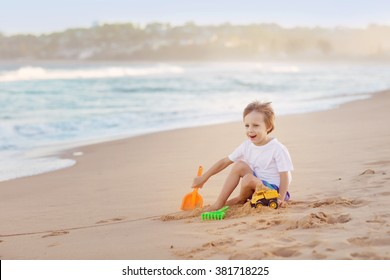 Cute little boy playing with sand and toys on a beach