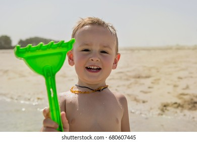 Cute little boy playing with sand tool at the beach. Portrait, close-up