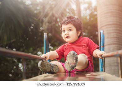 Cute little boy playing slide at the playground, looking down with surprised face, Active child playing outdoors in the sunny day