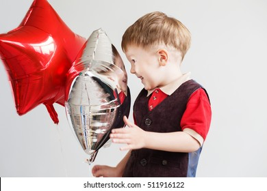 Cute little boy playing with star-shaped balloons in front of white background. Kid looks and rejoices at his reflection in foil balloon. Child laughing looking at the reflection in a distorted mirror