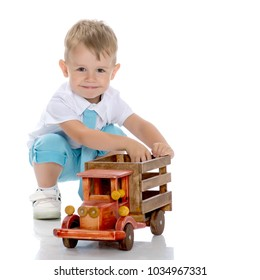 Cute little boy is playing with a toy wooden car on a white background in the studio. The concept of a happy childhood, learning and education in the family. Isolated.