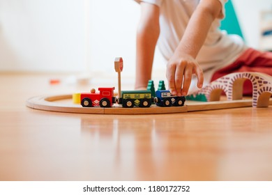 Cute Little Boy Playing With Toy Railroad At Home, Closeup