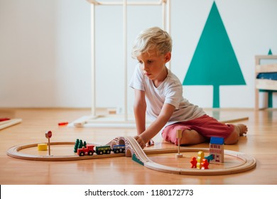Cute Little Boy Playing With Toy Railroad At Home
