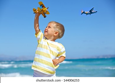 Cute little boy playing with a toy airplane against blue sky