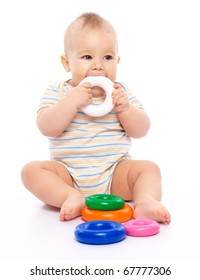 Cute little boy is playing with toys, biting one of them, while sitting on floor, isolated over white