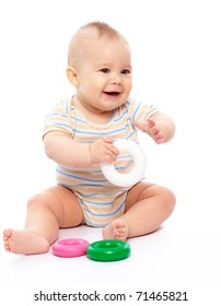 Cute little boy is playing with toys while sitting on floor, isolated over white