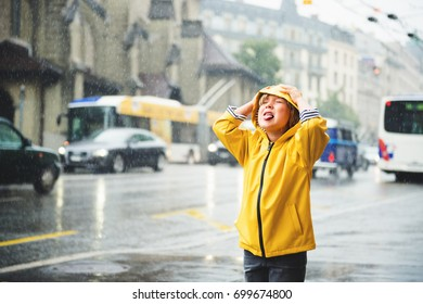Cute little boy playing under the, catching water drops by his mouth, wearing bright yellow raincoat with hood. Image taken in Saint-Francois square, Lausanne, Switzerland